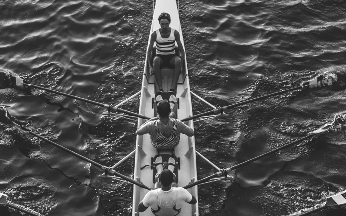 A rowing team out on the water with the cox at the head of the boat