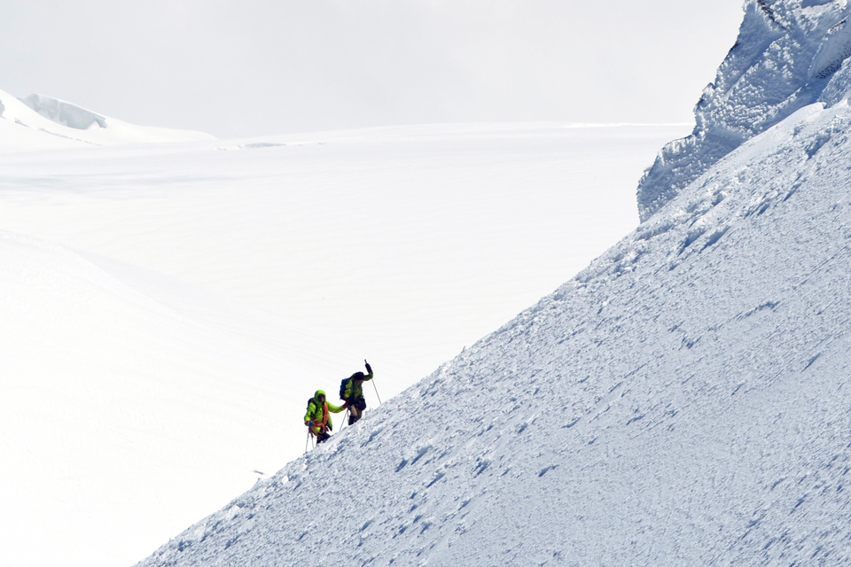 Two people climbing a mountain