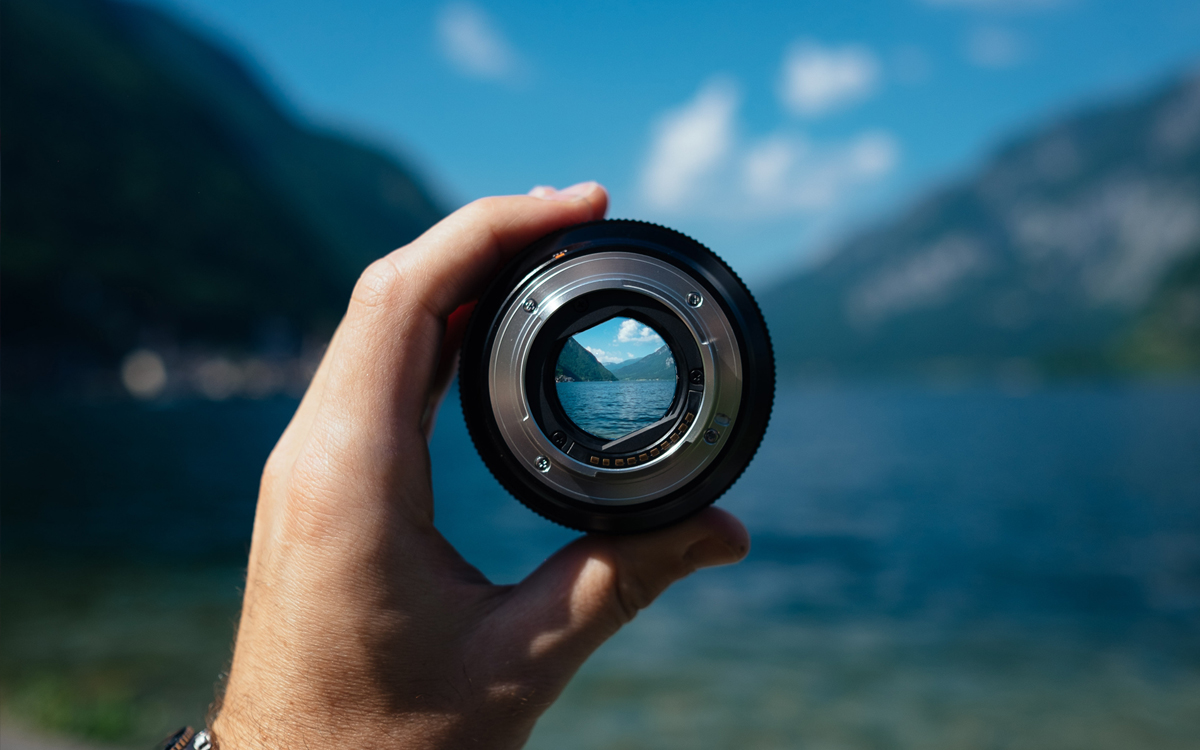 A lens held up to the landscape to focus in on something in the distance