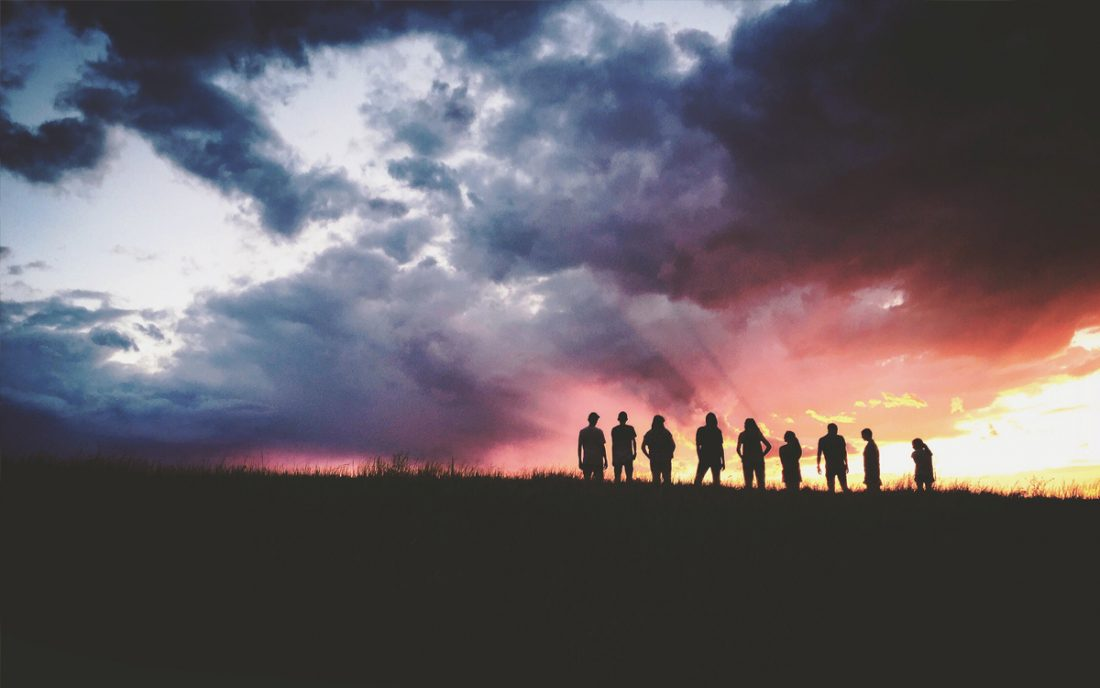 A team of people standing on a hillside in silhouette against a red sky